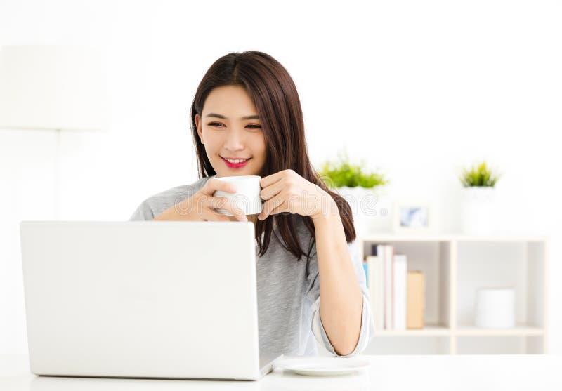 Mujer que trabaja en el ordenador portátil en sala de estar imágenes de archivo libres de regalías
