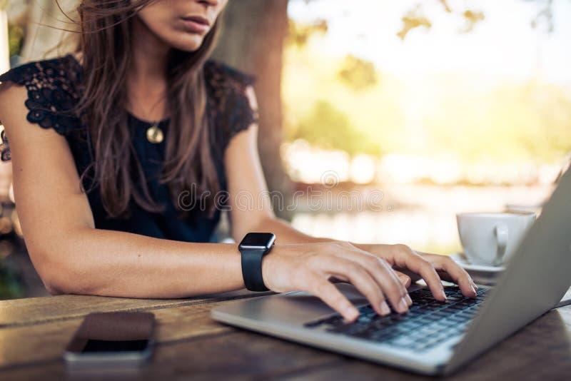 Mujer que trabaja en el ordenador portátil en un café al aire libre imagenes de archivo