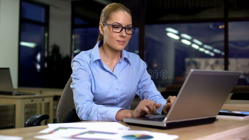 Mujer que trabaja en el ordenador portátil en el turno de noche, empleado motivado que trabaja en horas extras fotos de archivo libres de regalías