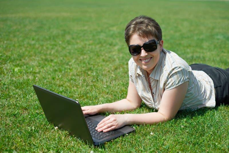 Mujer que trabaja en el ordenador portátil en el verano al aire libre, mentira en su vientre en el prado de la hierba verde, gent imagenes de archivo