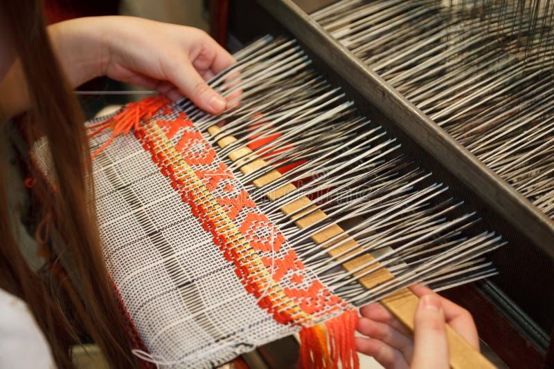 Mujer que trabaja en el telar. Artes nacionales rusos imagen de archivo