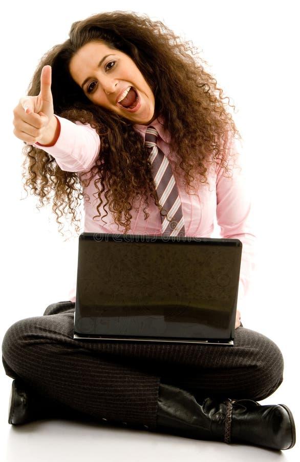 Mujer que trabaja en la computadora portátil con los pulgares para arriba fotos de archivo libres de regalías