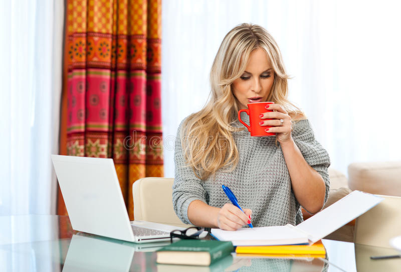 Mujer que trabaja en la computadora portátil en casa fotos de archivo