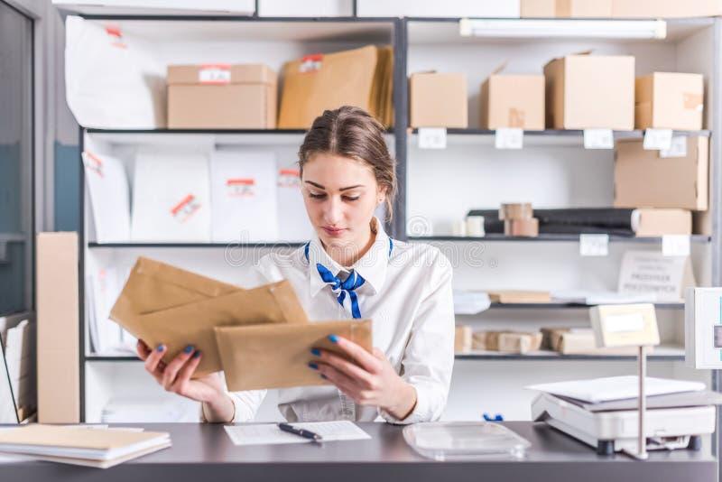 Mujer que trabaja en la oficina de correos imágenes de archivo libres de regalías