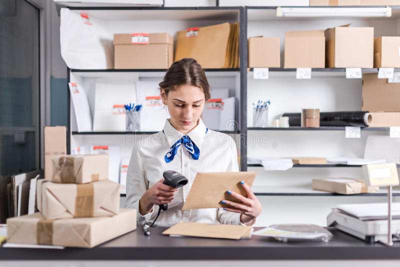 Mujer que trabaja en la oficina de correos fotos de archivo