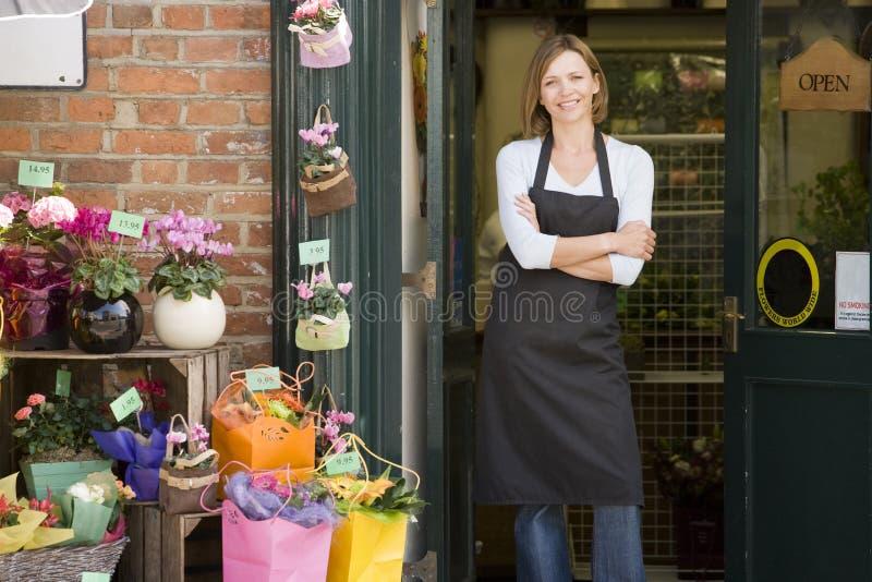 Mujer que trabaja en la sonrisa del departamento de flor foto de archivo
