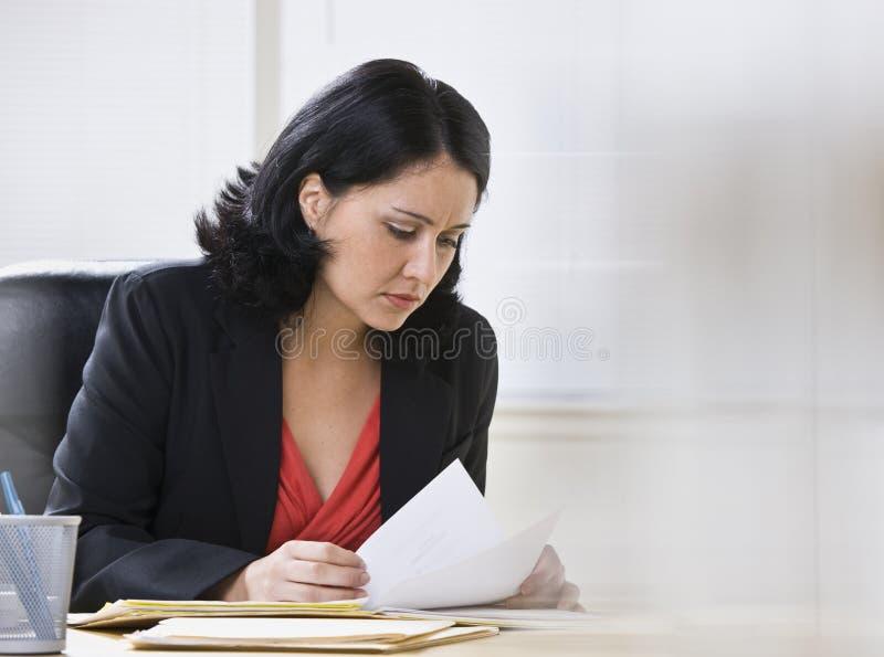 Mujer que trabaja en papeleo imagenes de archivo
