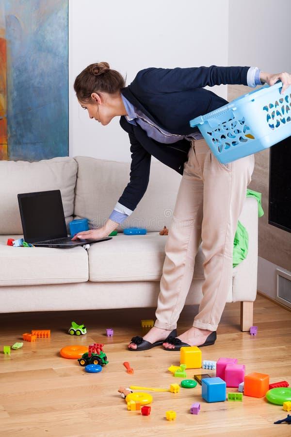 Mujer que trabaja en su ordenador portátil durante limpiar la sala de estar foto de archivo libre de regalías