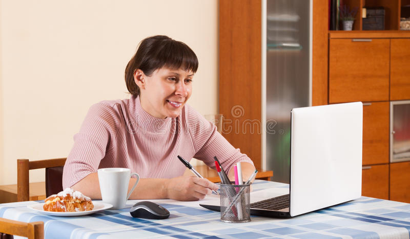 Mujer que trabaja en un ordenador portátil foto de archivo libre de regalías