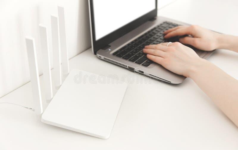 Mujer que trabaja en un ordenador portátil en casa Router blanco del wifi en el fondo blanco minimalism imagenes de archivo