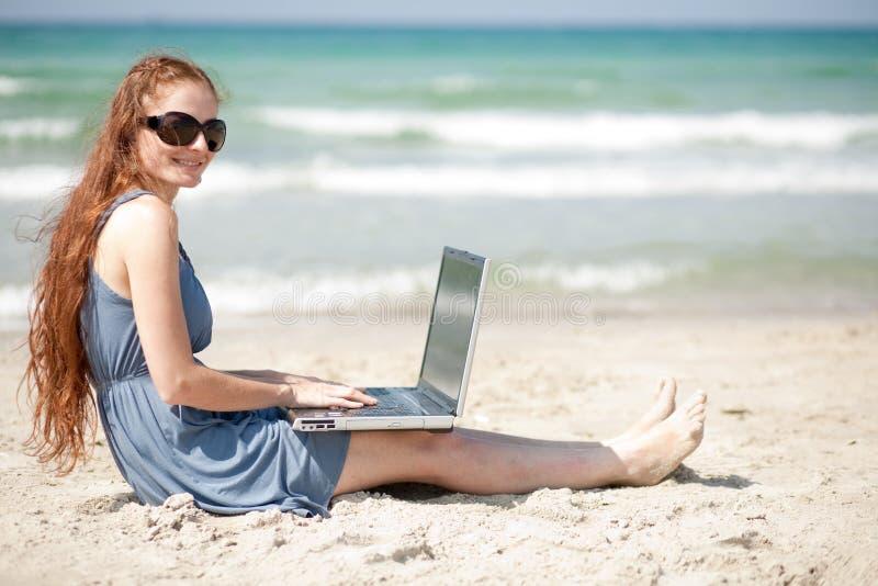 Mujer que trabaja en una computadora portátil sentándose en la playa fotos de archivo