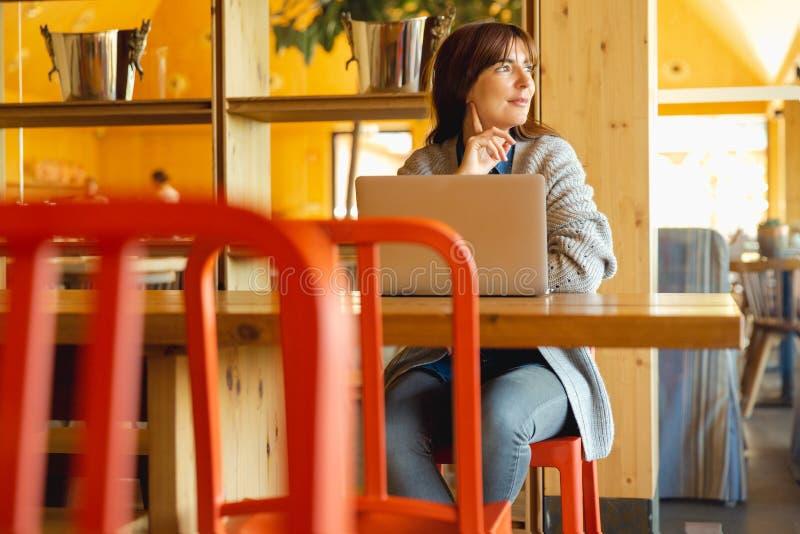 Mujer que trabaja en una computadora port?til fotografía de archivo