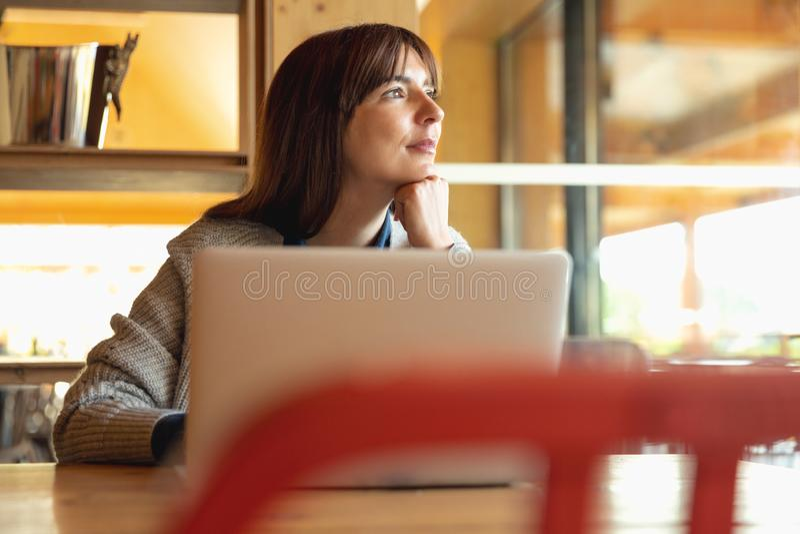 Mujer que trabaja en una computadora port?til foto de archivo