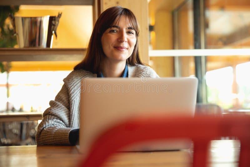 Mujer que trabaja en una computadora port?til imagen de archivo