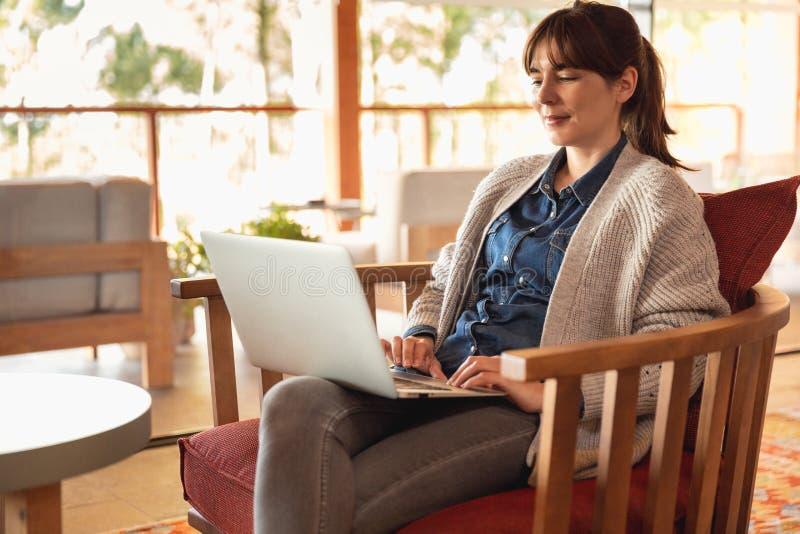 Mujer que trabaja en una computadora port?til fotos de archivo