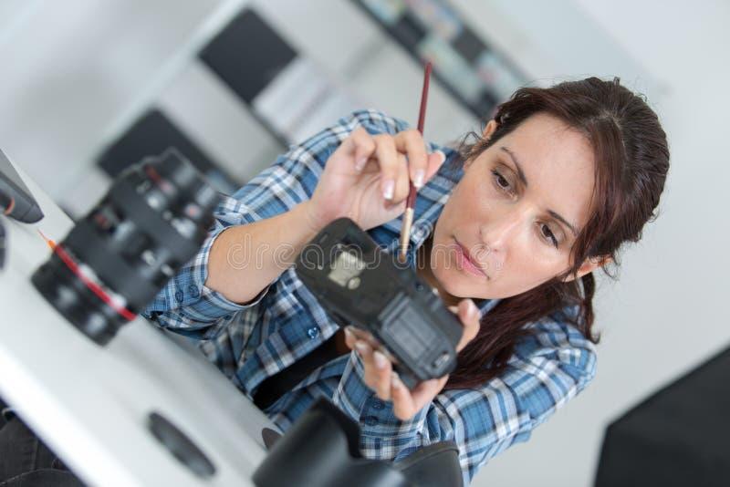 Mujer que trabaja en unidad del flash de la cámara fotografía de archivo libre de regalías