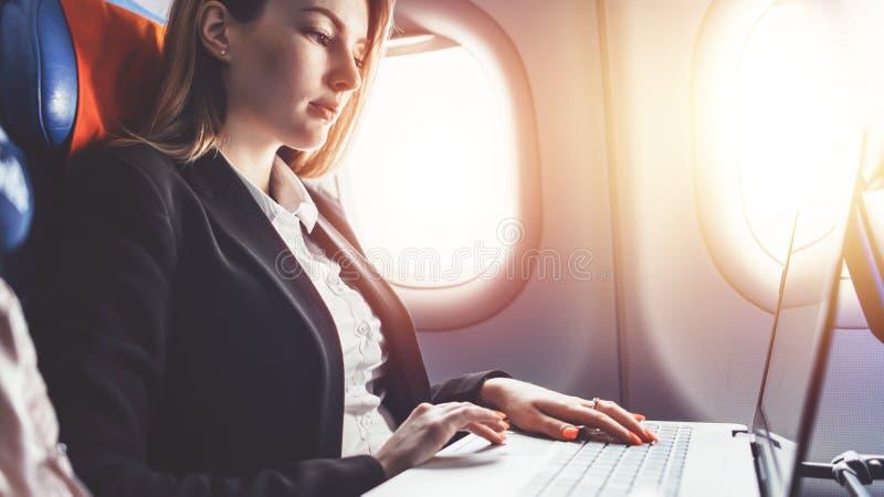 Mujer que trabaja usando el ordenador portátil mientras que viaja en avión imagen de archivo