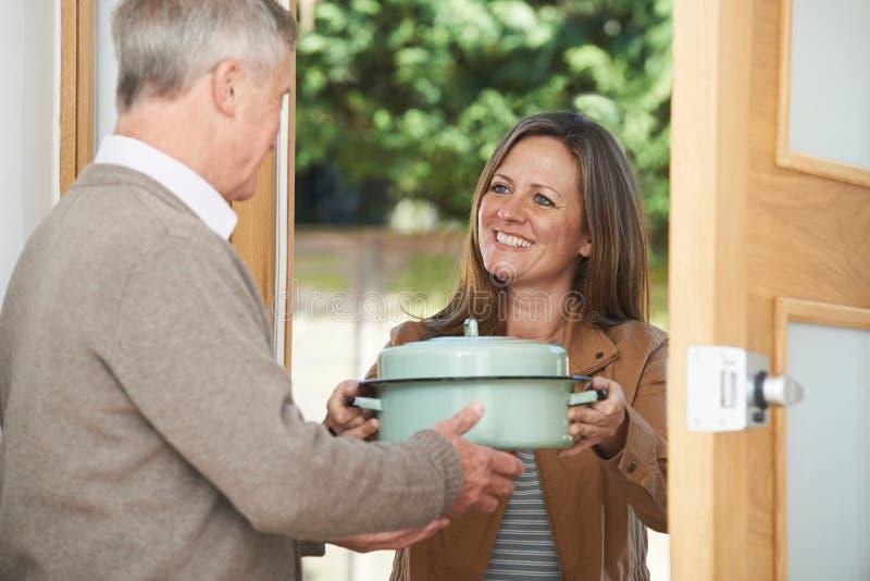 Mujer que trae la comida para el vecino mayor imagenes de archivo
