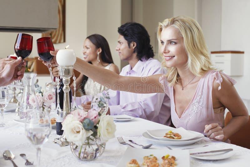 Mujer que tuesta el vino rojo con los amigos en la tabla de cena imagenes de archivo