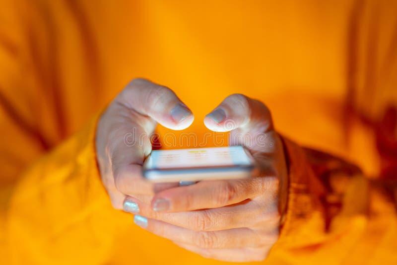 Mujer que usa cierre m?vil encima de la imagen conceptual del juego m?vil del apego del tel?fono y de los medios sociales imágenes de archivo libres de regalías