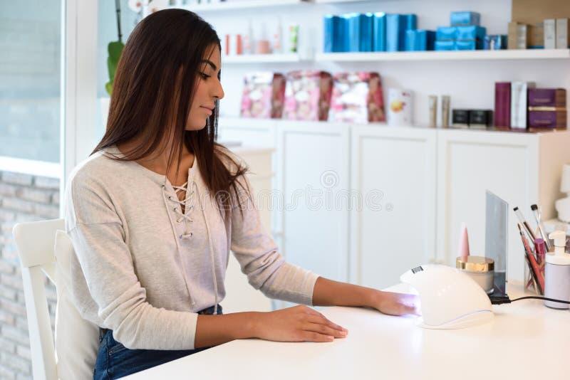 Mujer que usa clavos manicured en lámpara ULTRAVIOLETA imágenes de archivo libres de regalías