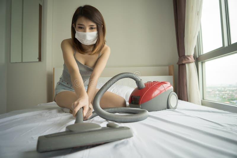 Mujer que usa el aspirador mientras que limpia la cama blanca en el homeBeau imagen de archivo libre de regalías
