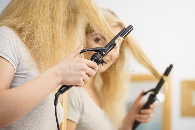 Mujer que usa el bigudí de pelo fotografía de archivo