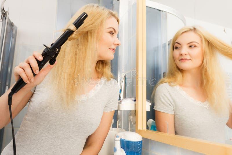 Mujer que usa el bigudí de pelo imagen de archivo
