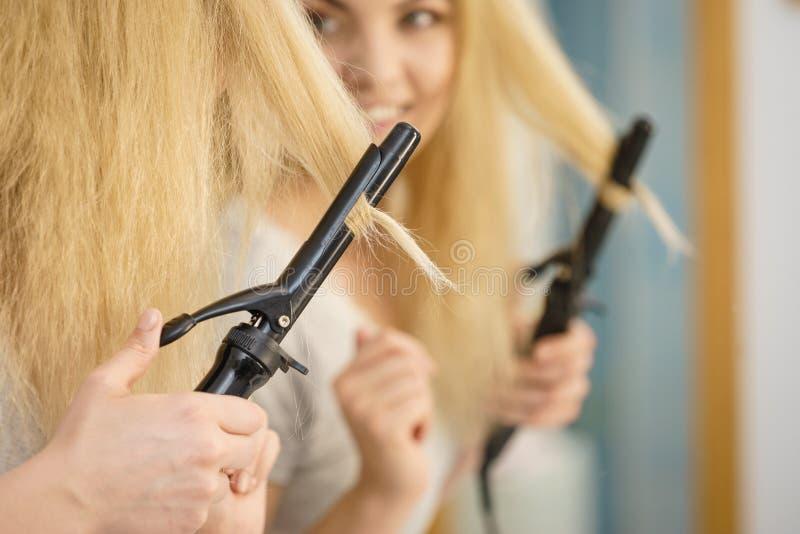 Mujer que usa el bigudí de pelo foto de archivo
