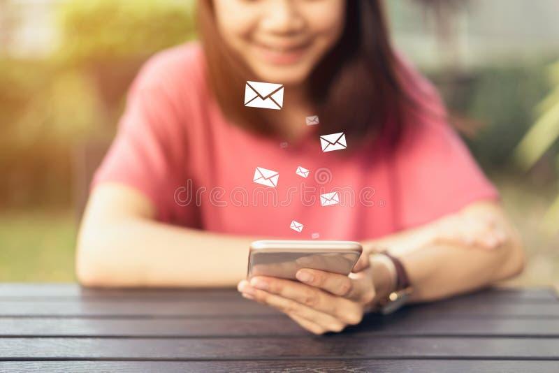 Mujer que usa el correo electrónico social del icono del smartphone y de la demostración, concepto de comunicación y de trabajo e foto de archivo libre de regalías