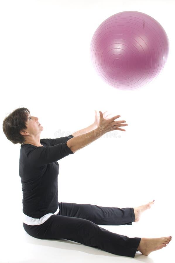 Mujer que usa el ejercicio de la bola de la aptitud del entrenamiento de la base imagenes de archivo