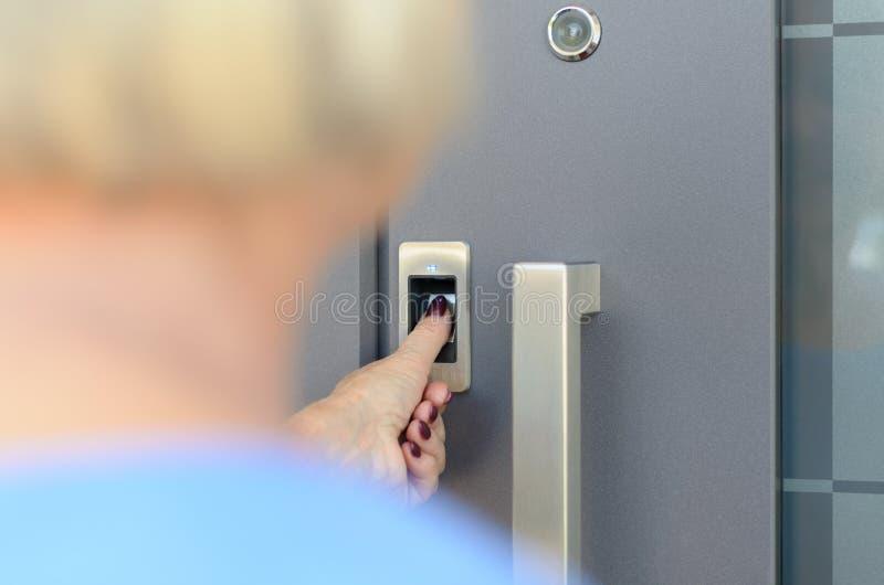 Mujer que usa el escáner para leer su impresión del pulgar imagen de archivo
