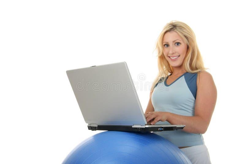 Mujer que usa el escritorio de la bola del ejercicio fotografía de archivo