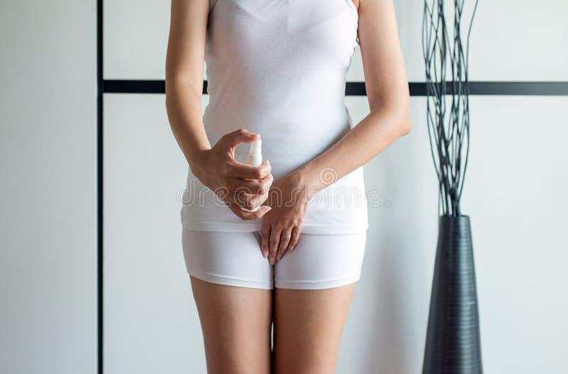 Mujer que usa el espray con leucorrhoea y dolor en abdomen o la descarga con el olor asqueroso fotos de archivo