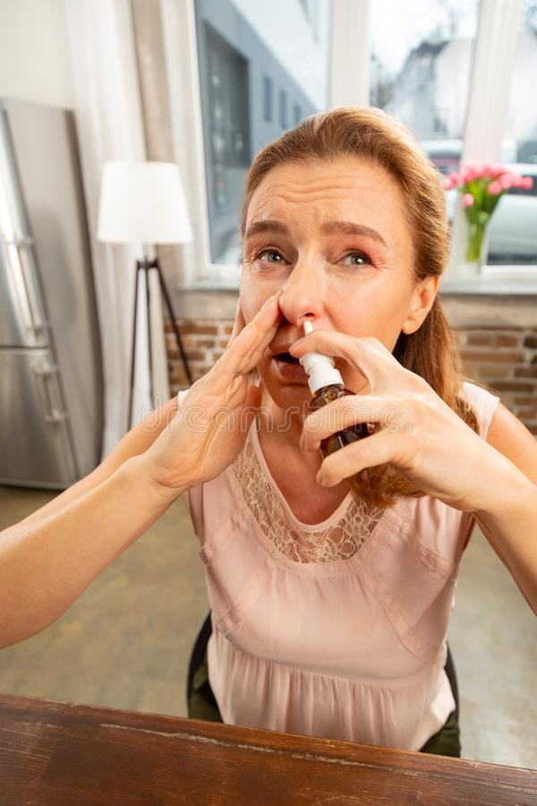 Mujer que usa el espray de nariz mientras que teniendo nariz corriente después de alergia foto de archivo libre de regalías