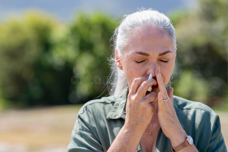 Mujer que usa el espray nasal para la alergia fotografía de archivo