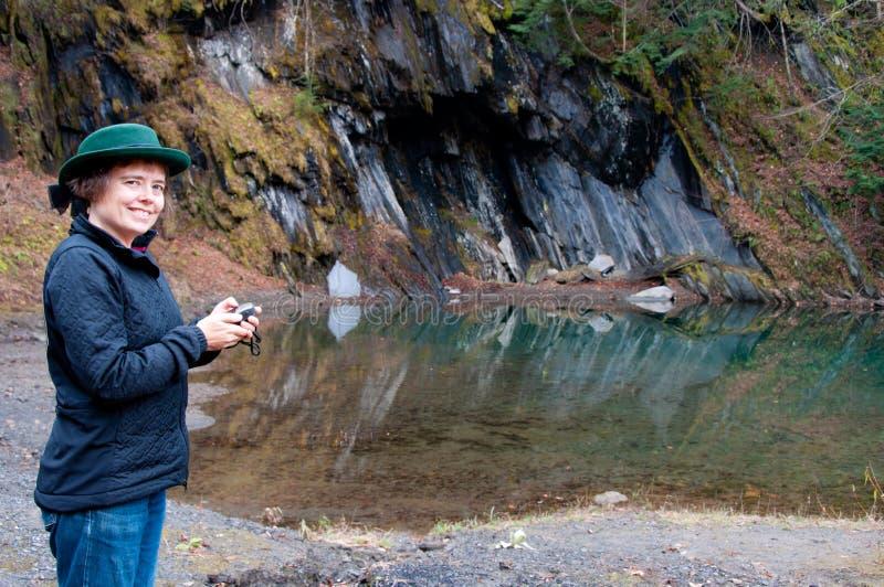 Mujer que usa el GPS por una piscina de la montaña foto de archivo libre de regalías