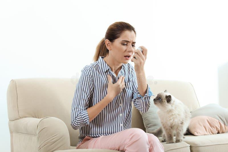 Mujer que usa el inhalador del asma cerca de gato en casa imágenes de archivo libres de regalías