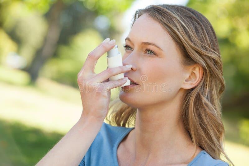 Mujer que usa el inhalador del asma en parque foto de archivo