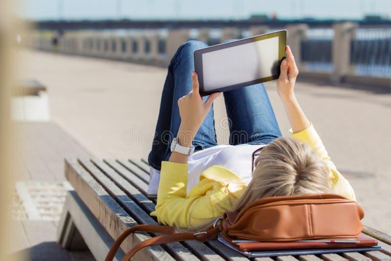 Mujer que usa el ordenador de la tablilla al aire libre fotografía de archivo libre de regalías