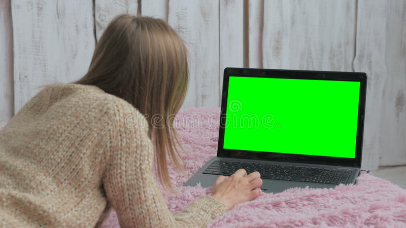 Mujer que usa el ordenador portátil con la pantalla verde imágenes de archivo libres de regalías