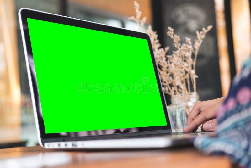 Mujer que usa el ordenador portátil con la pantalla verde en blanco en la tabla de madera en oficina fotografía de archivo libre de regalías