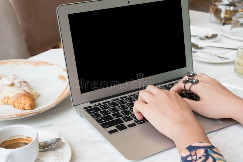 Mujer que usa el ordenador portátil con una taza de café fotografía de archivo