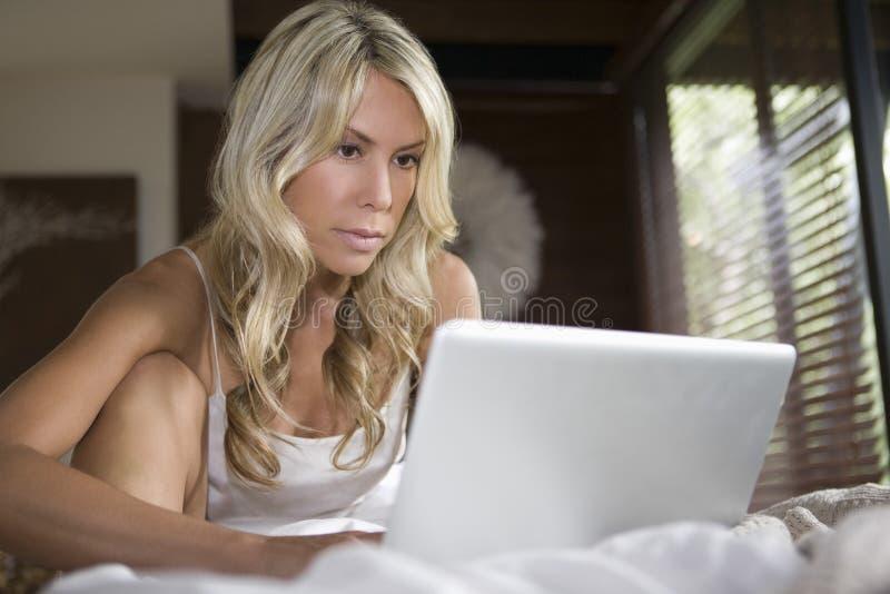 Mujer que usa el ordenador portátil en casa foto de archivo