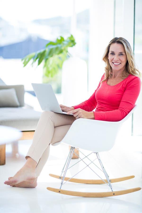 Mujer que usa el ordenador portátil en mecedora foto de archivo