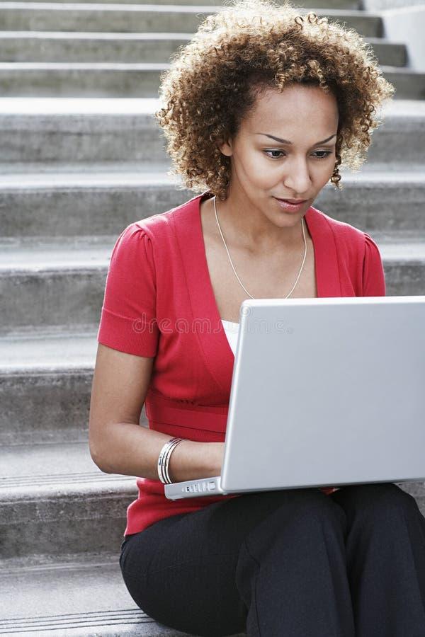 Mujer que usa el ordenador portátil en pasos al aire libre fotografía de archivo