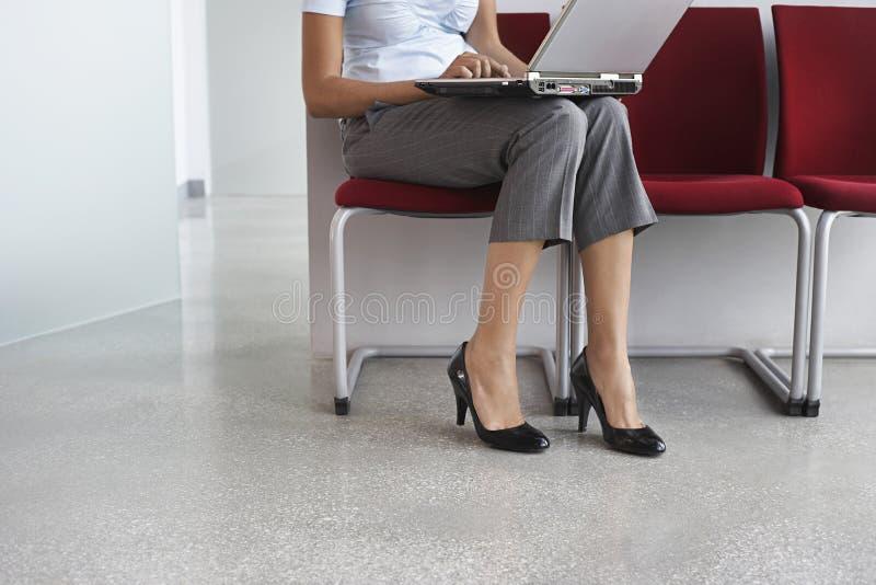 Mujer que usa el ordenador portátil en silla en pasillo imagen de archivo