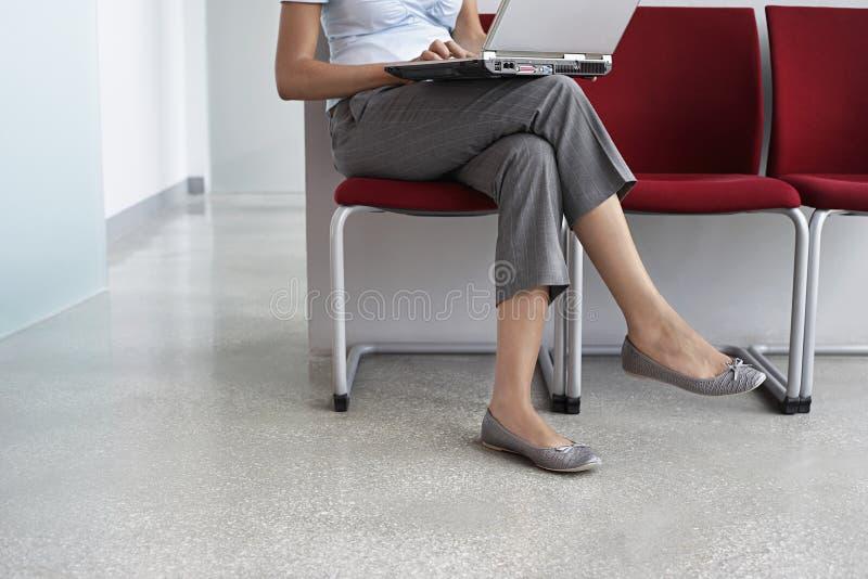 Mujer que usa el ordenador portátil en silla en pasillo fotografía de archivo libre de regalías