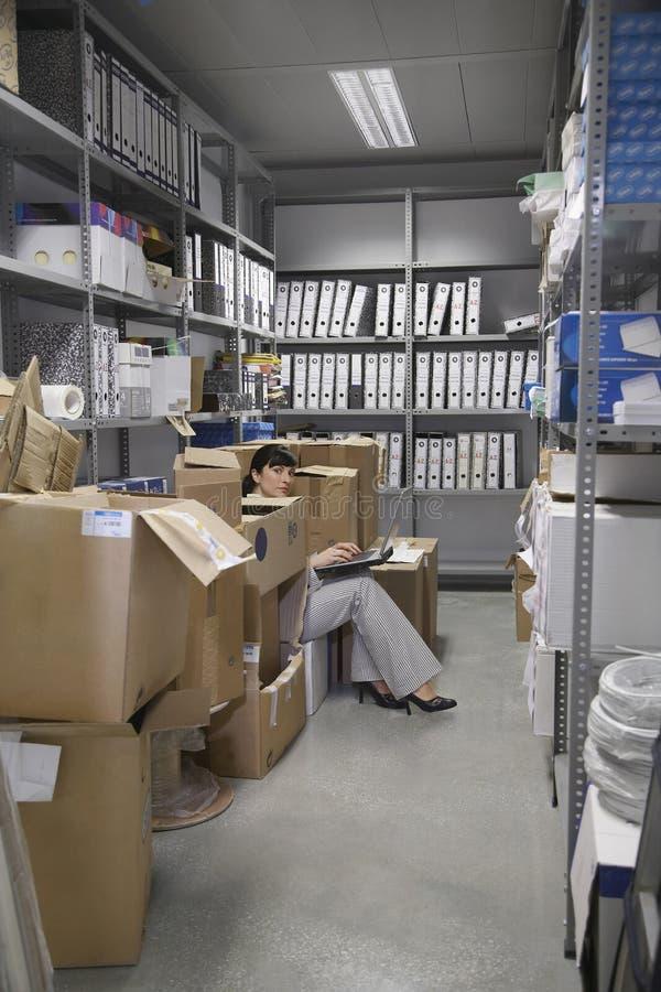 Mujer que usa el ordenador portátil en trastero de la oficina fotos de archivo libres de regalías