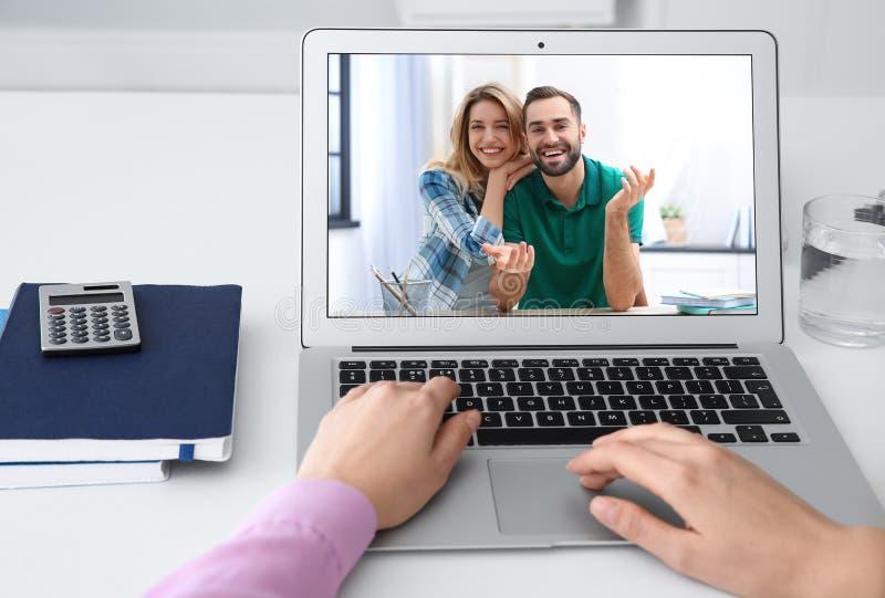Mujer que usa el ordenador port?til para la conversaci?n v?a la charla video en la tabla fotos de archivo libres de regalías